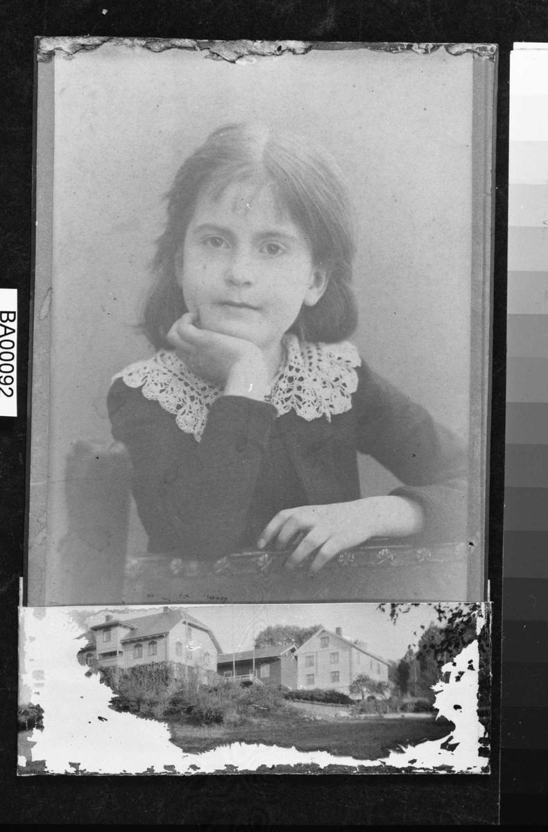 Portrett av pike (kanskje akkurat begynt i 1. klasse).  Hun sitter omvent på stol og støtter seg med ene albuen på rygglenet og hånden under haken, og andre armen liggende på kanten av stolryggen. Hun ser veldig våken ut og ser direkte på betrakteren.