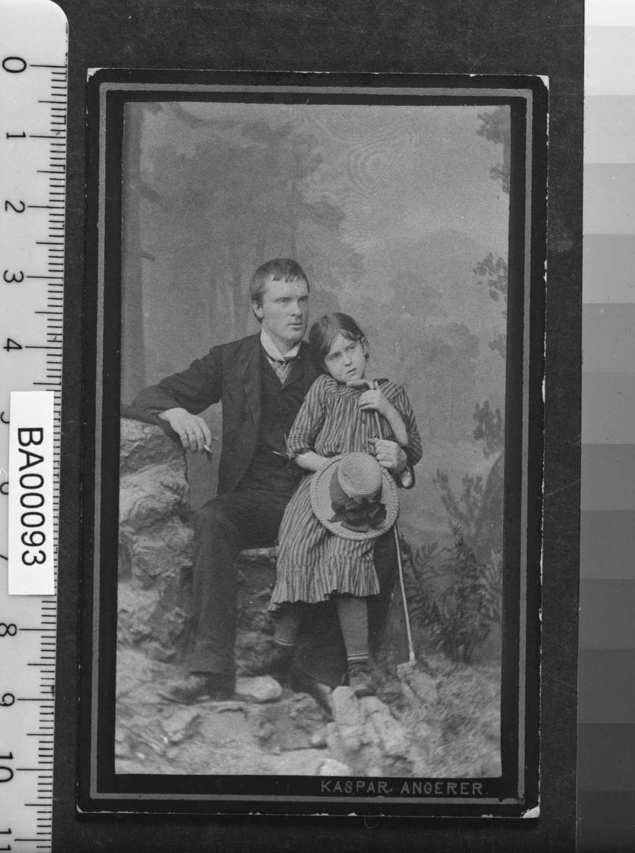 Atelierfotografi av voksen ung mann sittende med en stor pike på kneet og støttende seg til en lang stokk med ene hånd og holdende en sigarett i høyre hånd. Piken har også tak i stokken og i høyre hand holder hun en stor stråhatt med bredt bånd og sløyfe. Bakgrunnen viser et fjelllandskap.