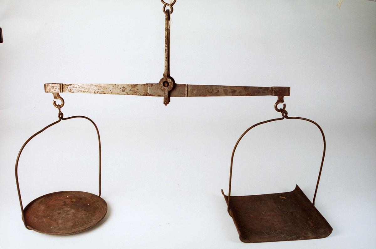 En rund og en firkantet vektskål. Under den runde skålen er det loddet et stykke jern forat skålene skal bli likevektige.