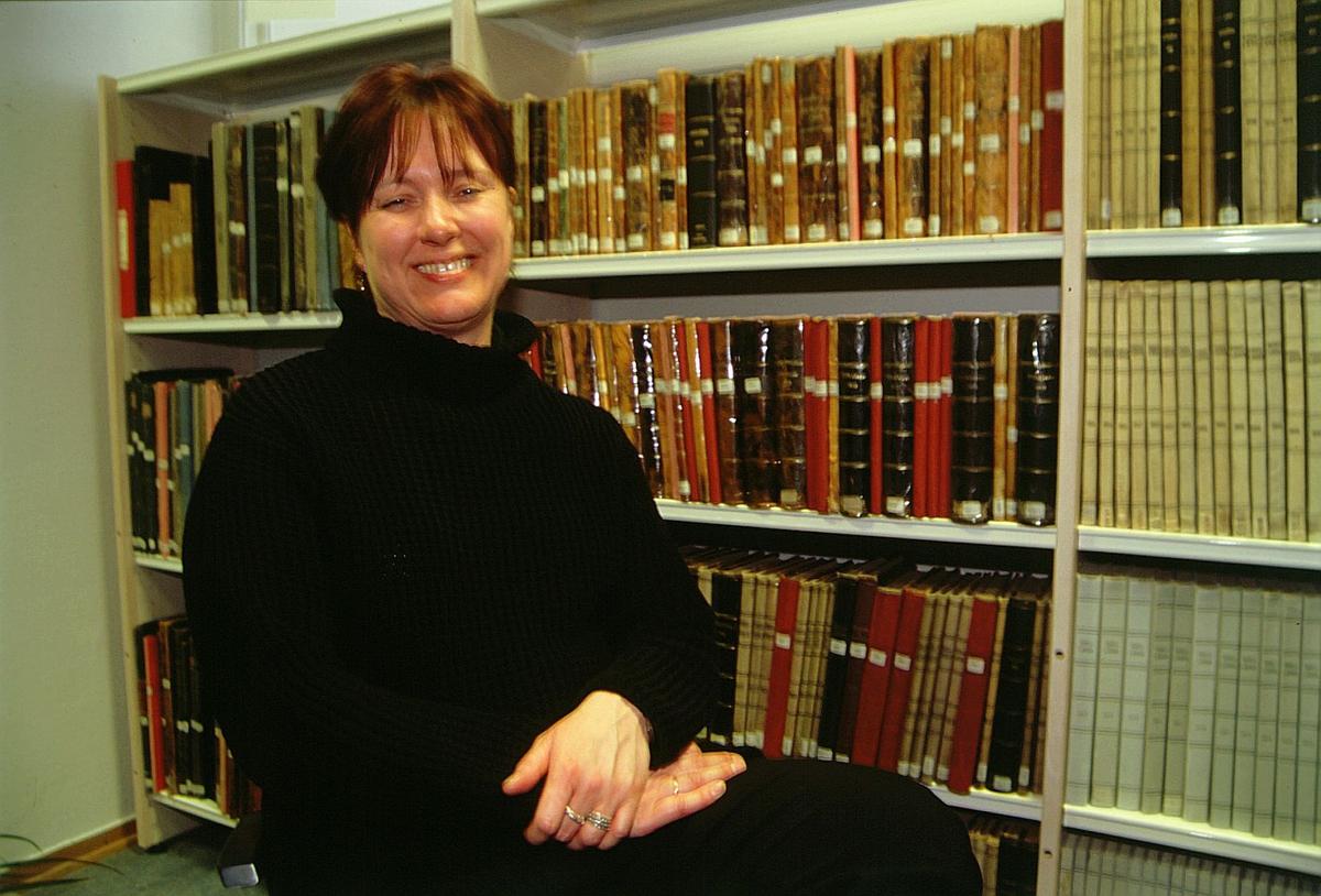 postmuseet, Kirkegata 20, biblioteket, Elin Eskerud står foran bokhyller med Sirkulære