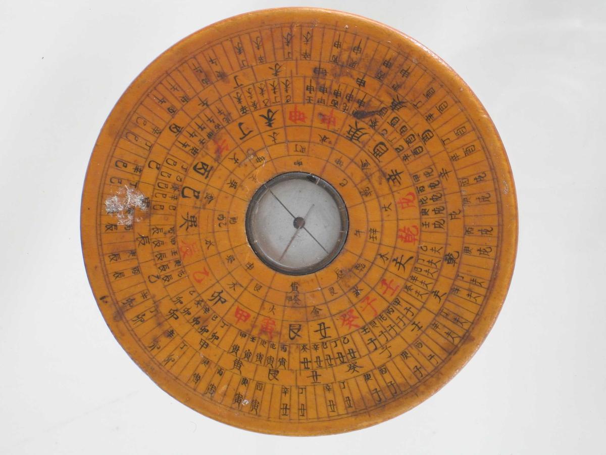Kompass av tre,  glass, metall.  På oversiden en detaljert  gradering i ulike retninger og tekst (kinesiske skrifttegn). Kompassnålen er bare 1,5 cm lang og på tykkelse som en  knappenål. Underlaget er en metallplate som er delt i to av en sort  strek. Kompasset er  tilnærmet bolleformet, men helt flatt.  På undersiden 8 skrifttegn. Tilstand sommer 1966: god.