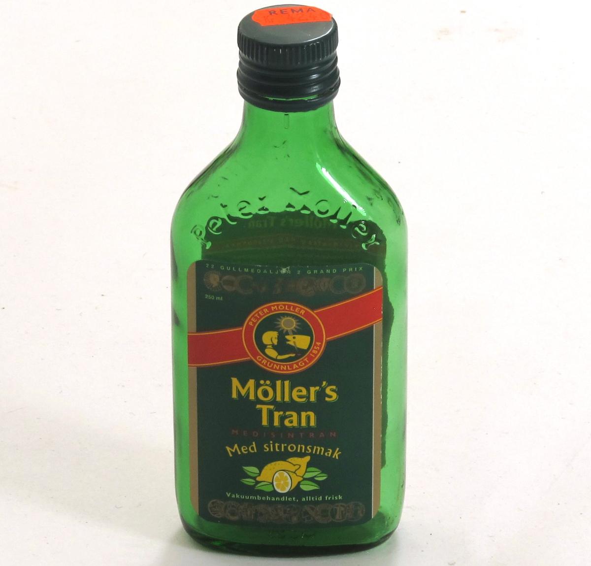 Flaske av grønnfarget glass, med grønn etikett, til  tran. 220 g.  Etikett med opplysninger om  innhold og oppbevaring, varemerke, utmerkelser og strekkode.