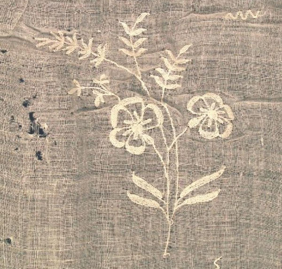 Små blomster på overdel og øverst på skjørtet. Større blomster og blader, samt bølgebord nederst på skjørtet. Hullbord i nedrekant.