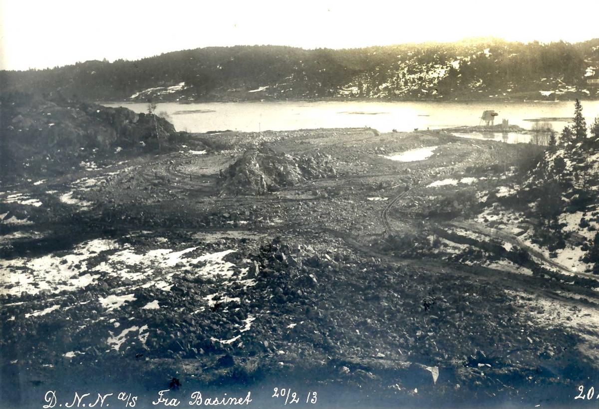"""""""20/02-1913"""" Nitriden. Fabrikktomten planeres.  Tromøysund og Tromøy i bakbrunnen. Fyrlykt nr. 612 i Norsk Fyrliste til høyre, bygd 1894, flyttet til Friisøy i 1929."""