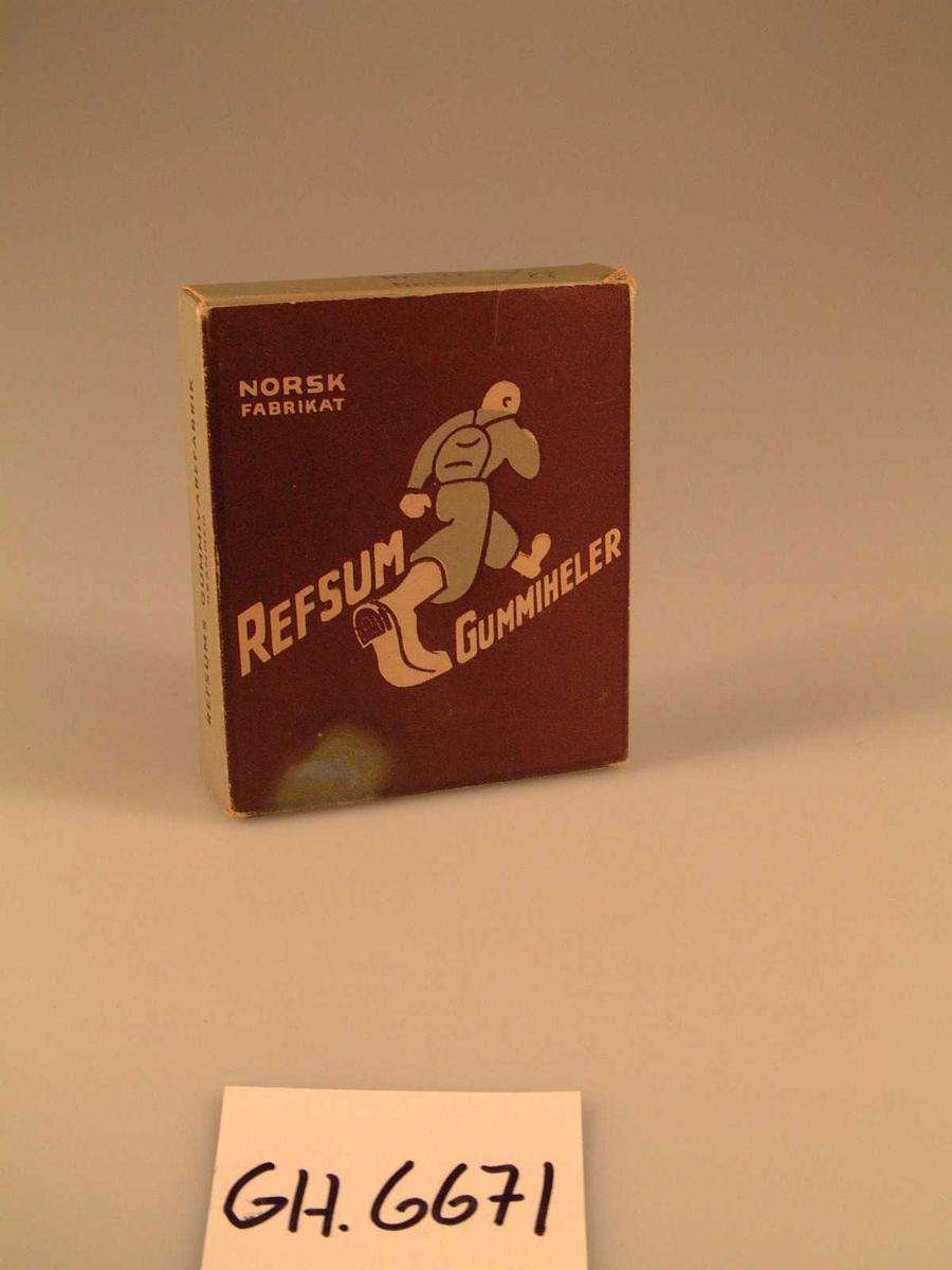 Rektangulær eske med åpning i begge kortender. Bilde av en hestesko med påskrift på den ene siden, bilde av en gående person på andre siden. Innhold: To hæler med en liten pose med stifter.