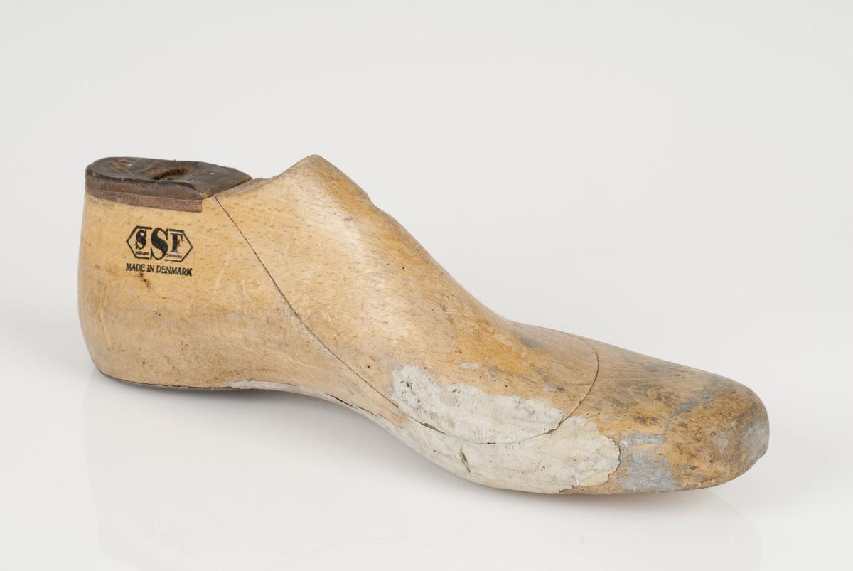 En tremodell i to deler; lest og opplest/overlest (kile). Venstrefot i skostørrelse 45, og 8 cm i vidde. Hælstykket i metall. Lestekam i skinn.