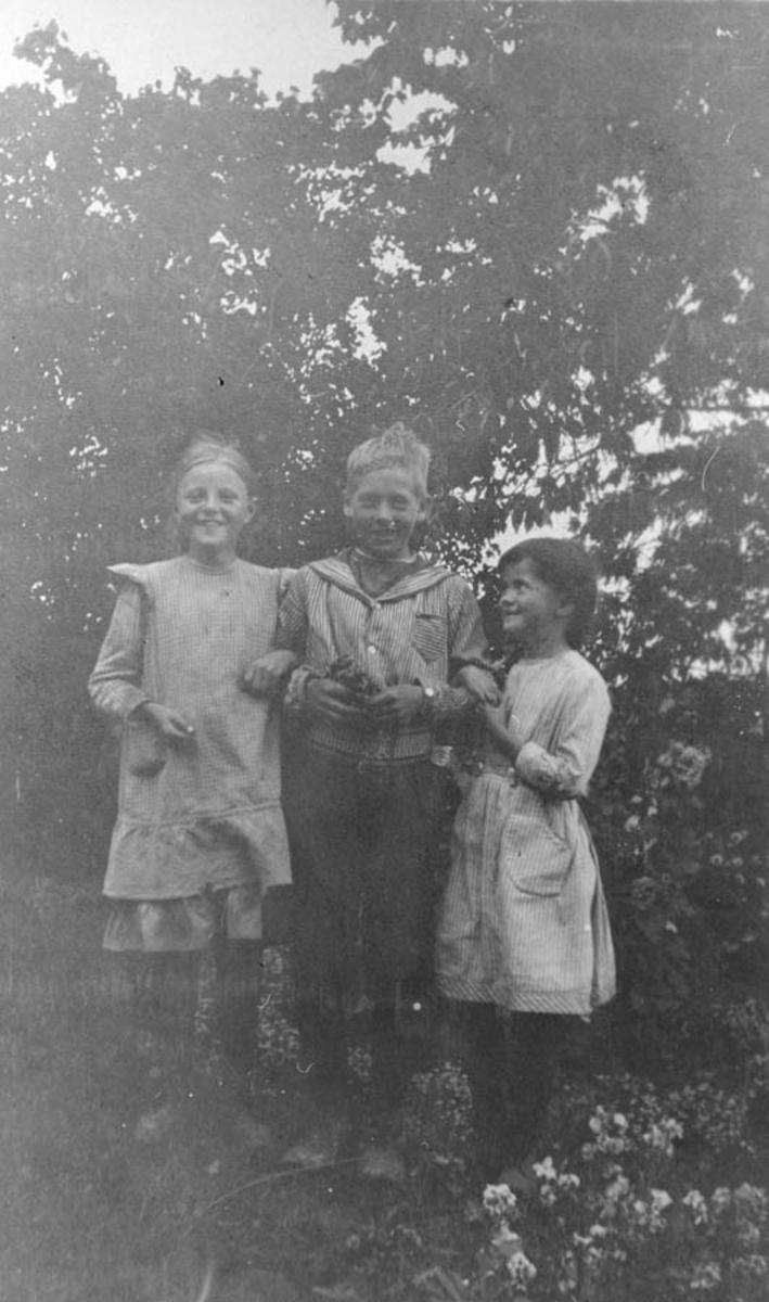 Tre barn i hagen på Ambjørnrud.