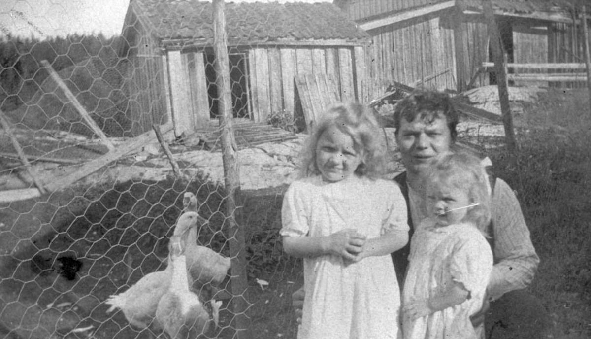 Mann og to jenter foran andedammen med gjess på gården Thoug.