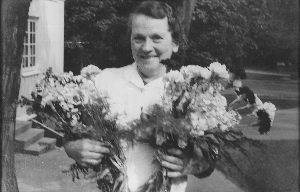 Kvinne med 2 blomsterbuketter