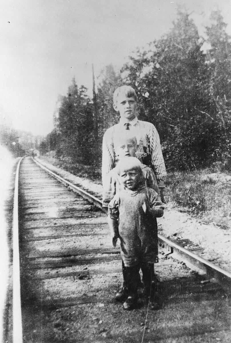 Tre barn på jernbanelinja.