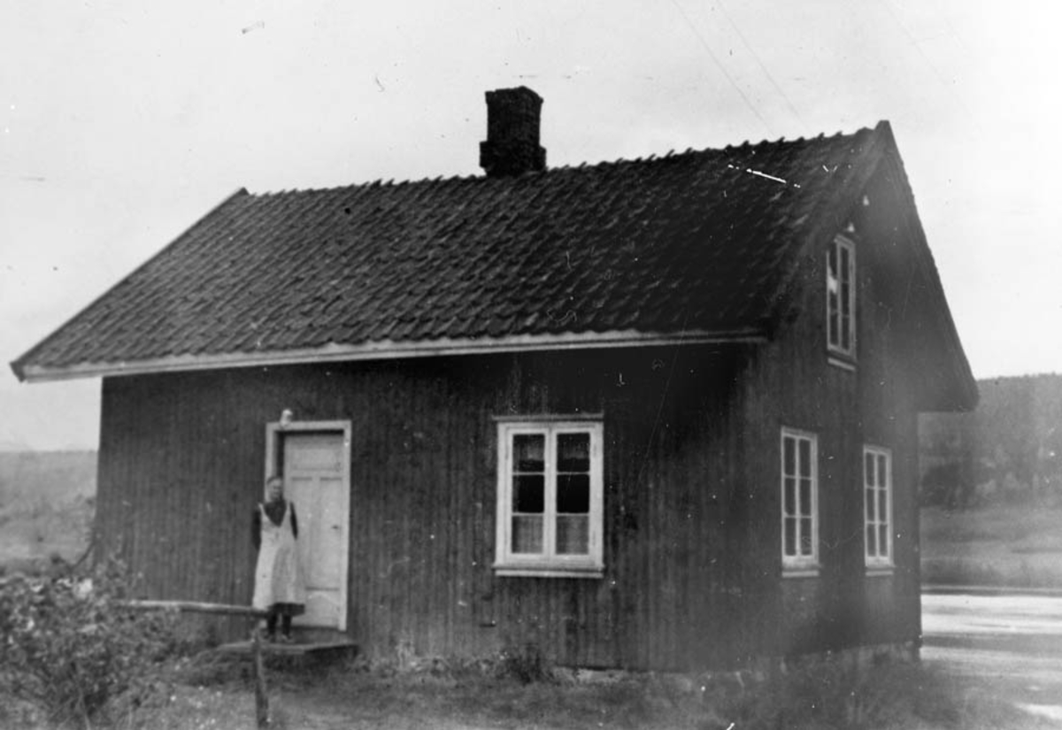 Huset i enga. Inga Høybråten står på trappa.