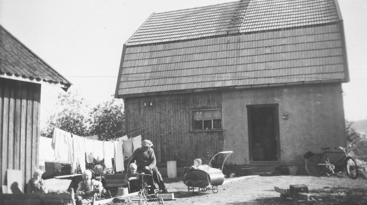 Dagligliv i tunet. Barna leker i sandkassa med biler og trehjulsykkel, et barn i barnevogn. Klær til tørk på snor mellom husene. En voksen mann ser til barna. Sykkel parkert på hushjørnet.