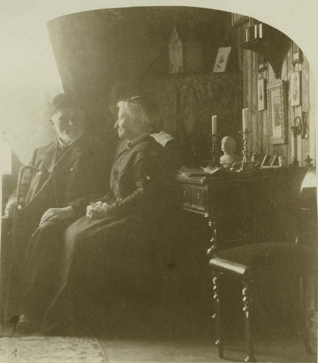 Eldre mann og kvinne sitter foran et skrivebord