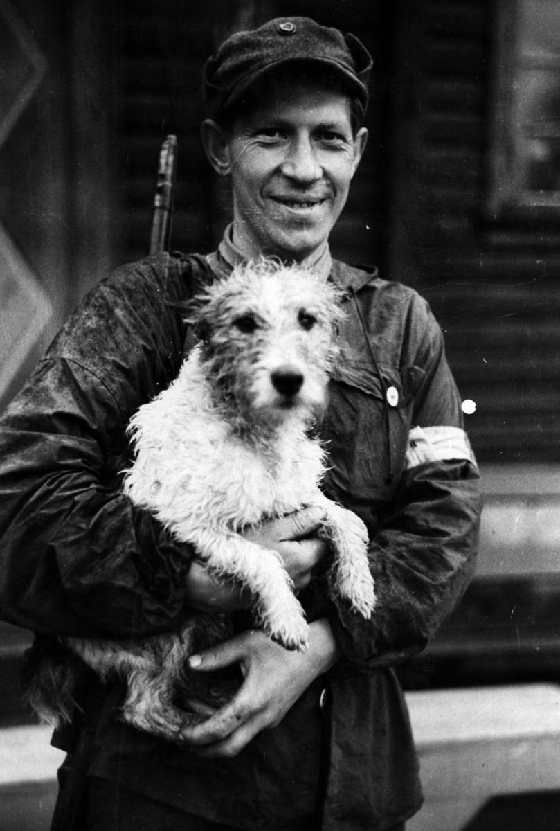 Uniformert mann med hund på armen.