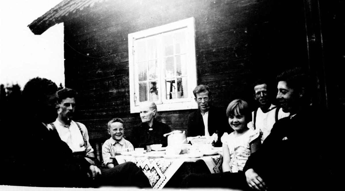 Husmannsplass. 5 menn, 3 røyker pipe, 1 eldre kvinne, en gutt og en pike samlet rundt dekket kaffebord utenfor huset.