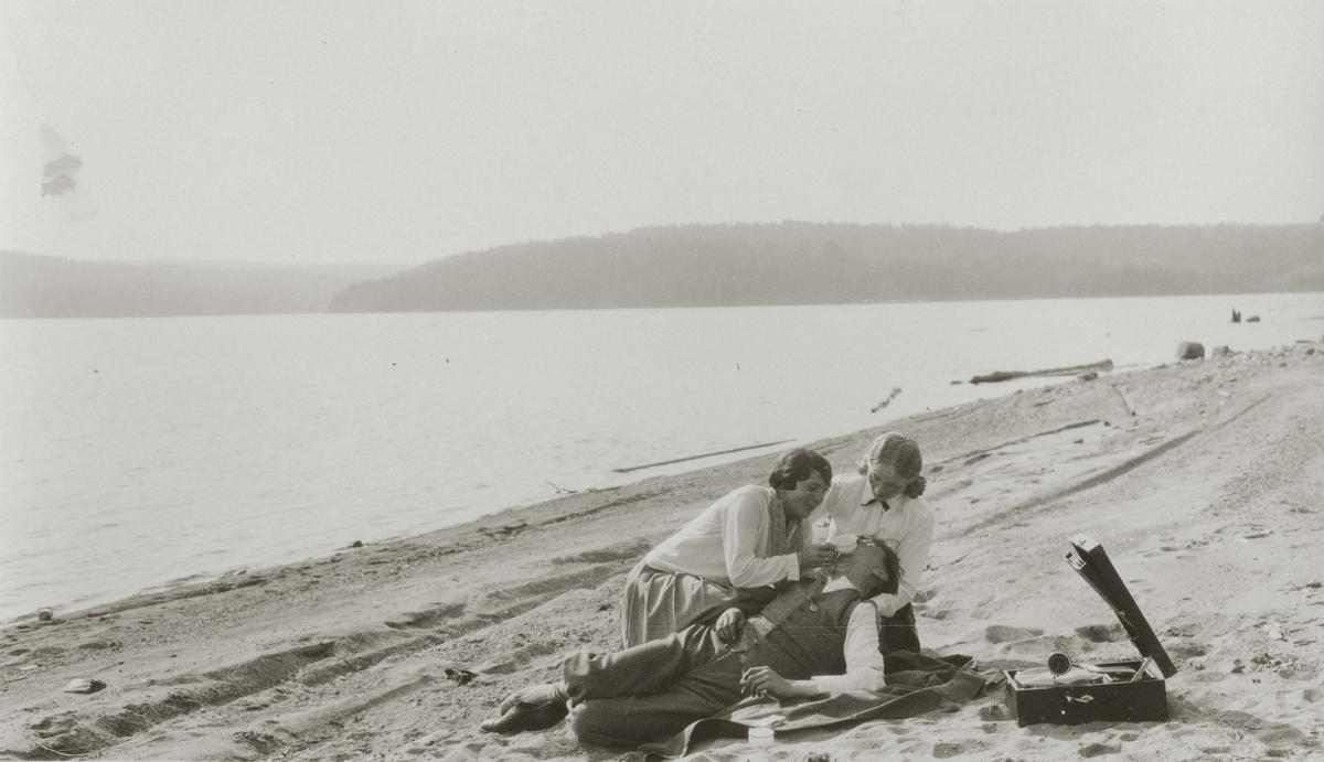 To damer og en mann på stranden med sigaretter og portabel grammofon.