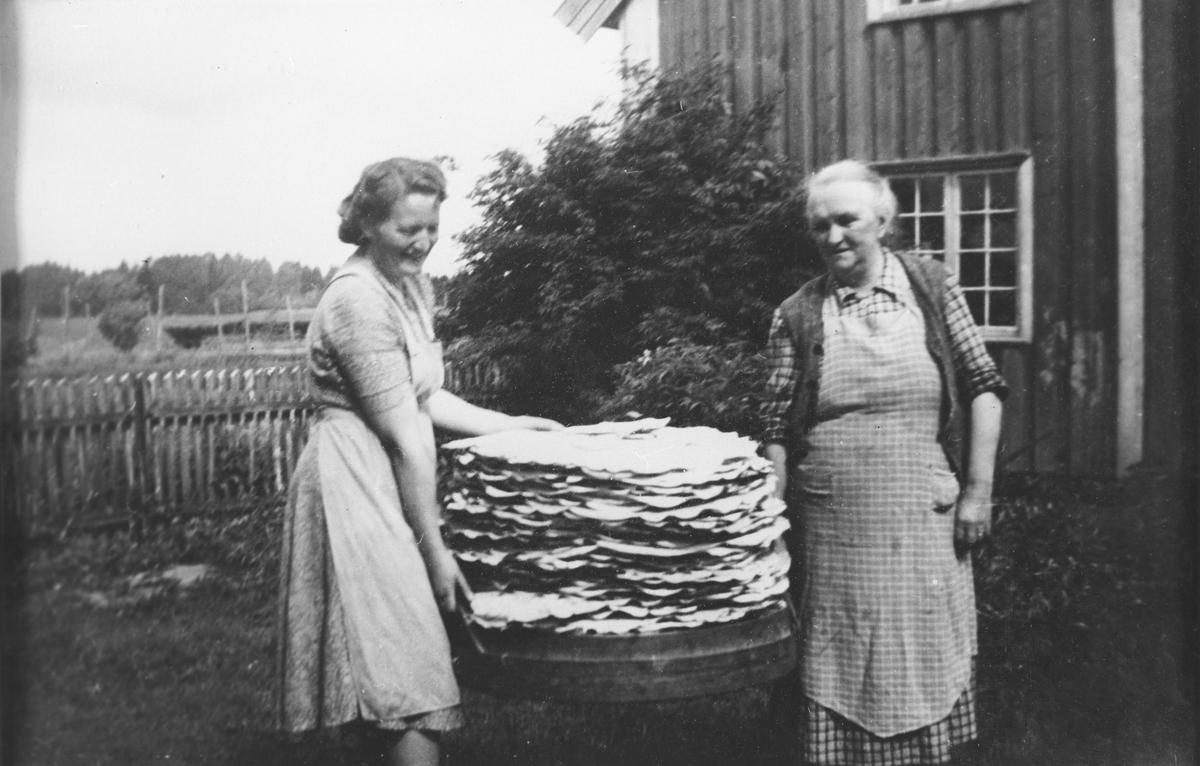 Flatbrødbakst  på Hovin. To kvinner bærer flatbrødstablen mellom seg.