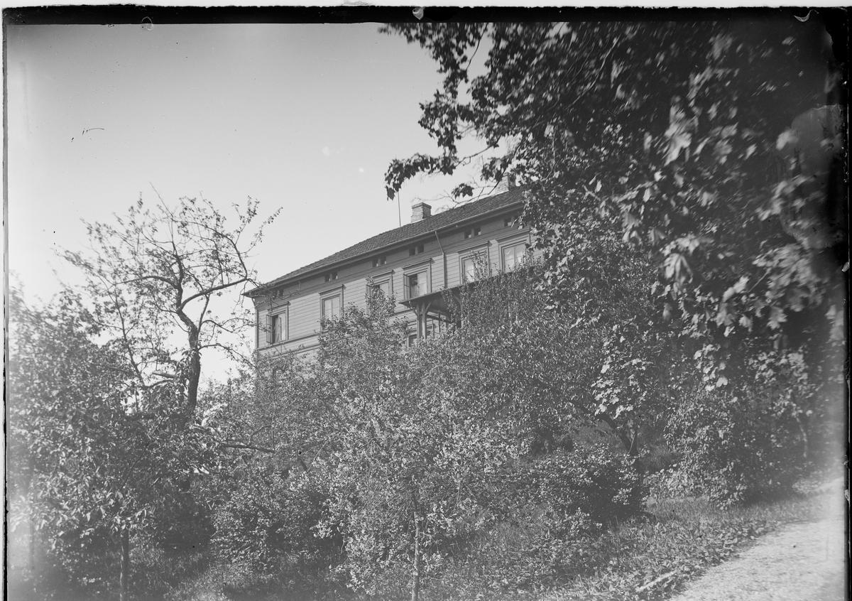 Huset på Linderud Gård sett gjennom trærne.