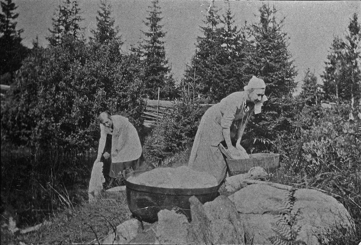Kvinner som vasker klær ved en bekk. Ca. 1911. Bildet er fra en plass ved Holtteie mellom Granly og brua over Holtåa. Dette var en felles vaskeplass for husstandene omkring. Kvinnene er sannsynligvis vesle-Maren og hennes mor Maren Langbakken. (Eidsvoll i gamle glimt).