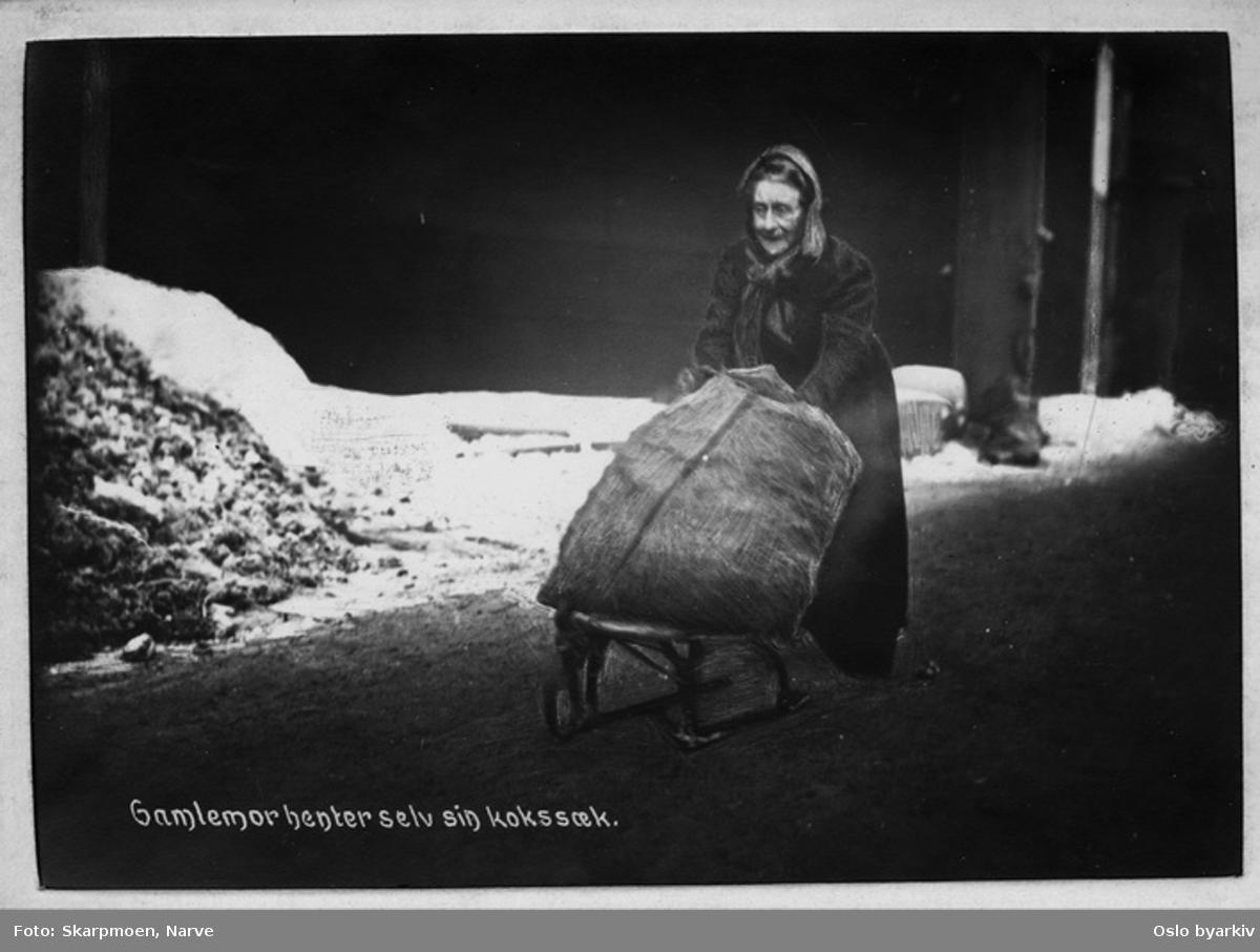 En gammel kvinne frakter en kokssekk på en kjelke (liten spark?), vinter med snø i gata.