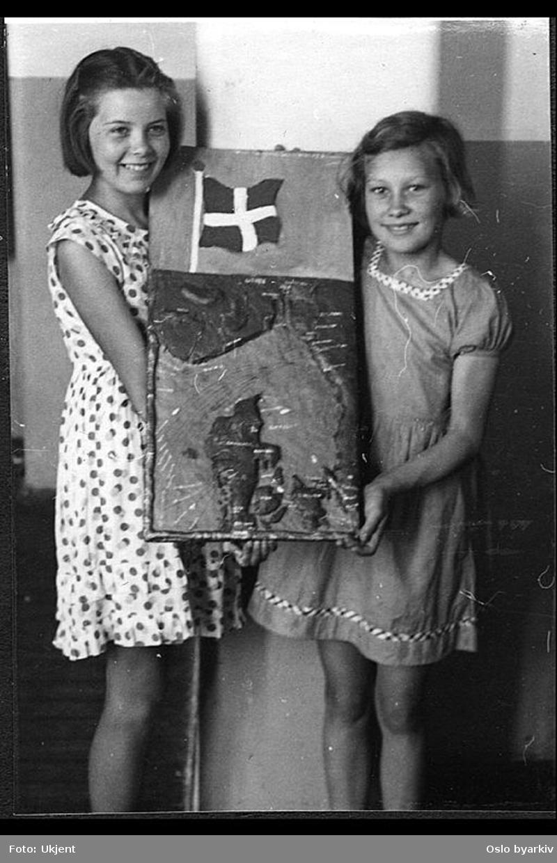 """To jenter viser fram et relieffkart av Danmark. Albumtittel: """"Sofienberg skole femti år - første september 1933."""""""