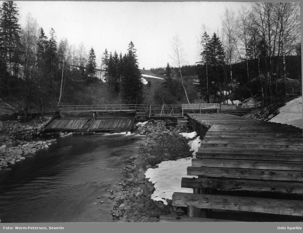 Kar i dammen og langs kanten som skal stoppe tømmeret. Elvebro. Plassen Grønvold i bakgrunnen. Akerselva, Frysja, Brekke.