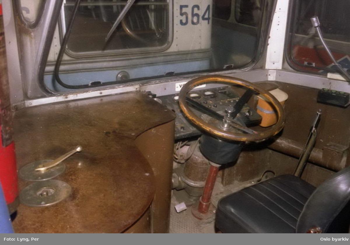 Oslo Sporveier. Trikk motorvogn 208 type Høka MBO, nærbilde av førerplass før ombygging til enmannsbetjening. I det store og hele uendret fra 1952, dog er det tilkommet orange plastbøtte for søppel, trykknapper for radio og høytalere (svart boks med grønne knapper og mikrofon) i 1975 samt vifteovn type PYROX (rør langs høyre vegg). Bærer preg av over 30 års slitasje.