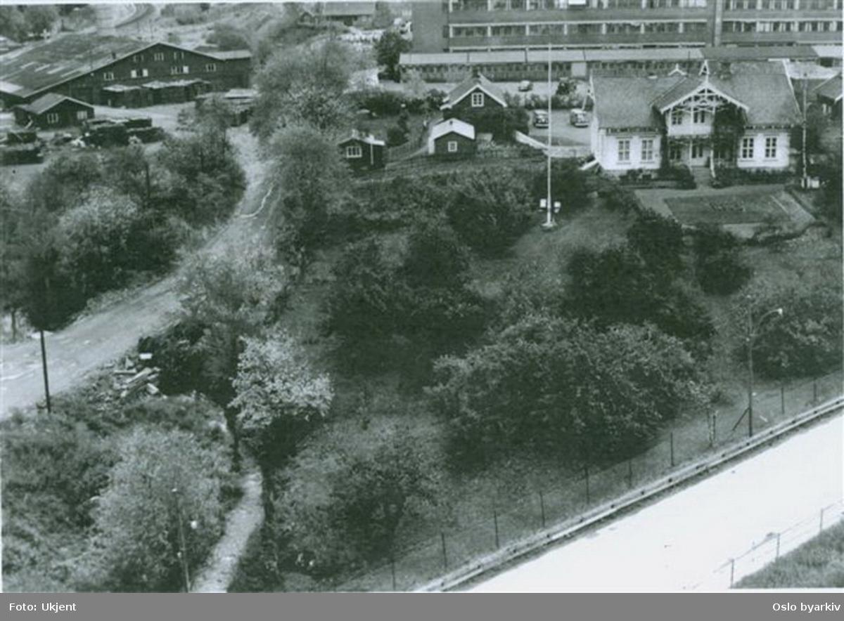 Hovedhuset på Mellom Hovin (revet 1997) og bygninger på STK i bakgrunnen. Daværende Østre Aker vei i bru over Hovinbekken, som fortsatt går åpen i forgrunnen. Bak ligger Akers teglverk (revet 1988). T-banens trasee sees så vidt i øvre bildekant. Bildet er tatt 1967 fra høyhuset i Ulvenveien 88.