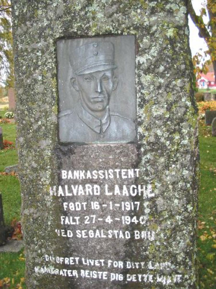 Ca 2 meter høy granittstein. Over teksten på steinen et portrett av Halvard Laache støpt/formet i kobber.