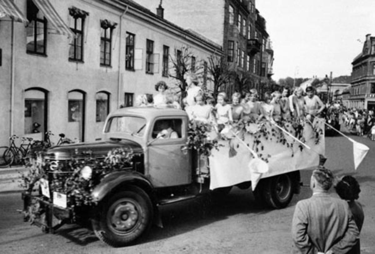 """HAMAR RØDE KORS. BARNEHAGEFONDET. BARNAS DAG 3. JUNI 1951. INNSAMLING TIL INNTEKT FOR NY BARNEHAGE. STOR BARNEKORTESJE. START HJØRNET PARKGT. /ST. OLAVSGT. KL. 16. RUTE PARKGT. STRANDGT. SKOLETORVET, TORVGT. ØSTRE TORG, VANGSVEGEN, ST. OLAVSGT OG TILBAKE TIL UTGANGSPUNKTET. BARN PÅ LASTEBILER UTKLEDD I KOSTYMER- MED HOV FOR INNSAMLING AV PENGER. VOLVO """"RUNDNOS"""" 1946-54 LASTEBIL"""