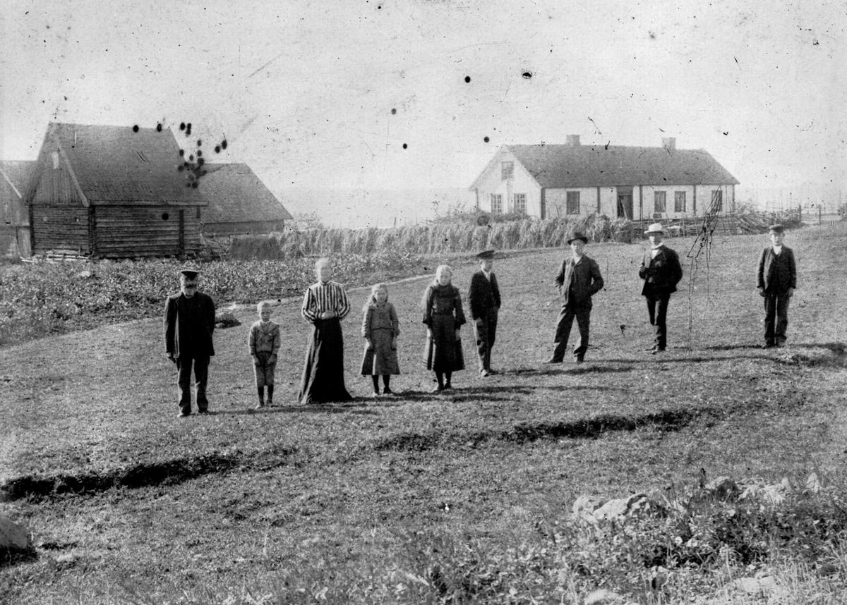 Gruppe personer foran bygninger på Maurud nedre, Helgøya. Lars Larsen Lier (1832-1910), Ottar f.1899, Teoline Torsdatter Fjeld (1853-1929) , Karen Sofie f.1895, Lovise f.1893, Torstein (1888-1971), Leonard (1885-1978), Torolf Hansen Vien f.1879, Magne (1891-1972).