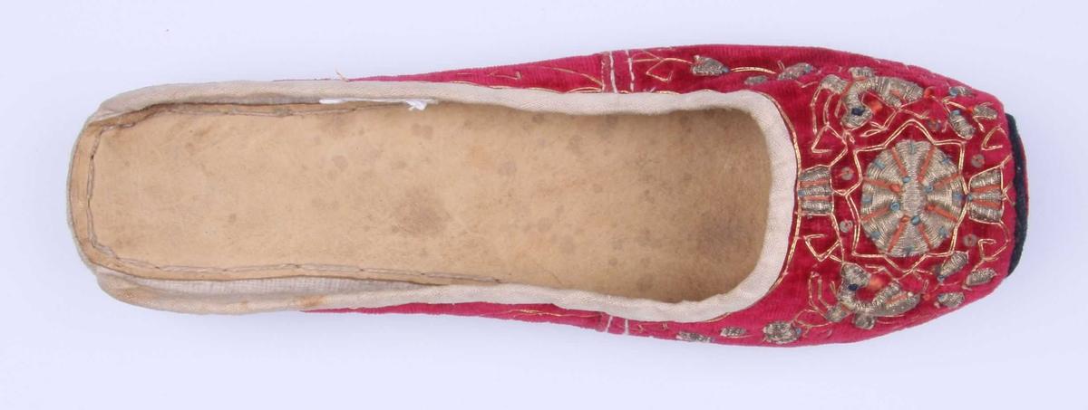 Tøffel av rød fløyel med gullbroderi på tåhetten og litt nedover sidene, med otteblads rosett og små blader omkring. Fine ranker innimellom sydd med dobbel gulltråd. De opphøyde partiene er brodert med gulltråd over tette lag av tråd. Tøffelen har rett avskåret tå, overdelen med flat snute dannet av halvsirkelformet halvt felt kantet med sort. Ingen helkappe. Fôr av hvitt lerret og kant langs utringningen av hvitt linlerret. Tynn skinnsåle innvendig. Sålen består av: en brun lærsåle kantet med hvit lerret og randsydd med hyssing, derunder en tykkere såle av hvitt ugarvet lær og helflikk. Dessuten såle av brunt garvet lær, randsydd med tykkere hyssing. I sålen og hælen noen huller hvor hyssing-ender stikker ut.