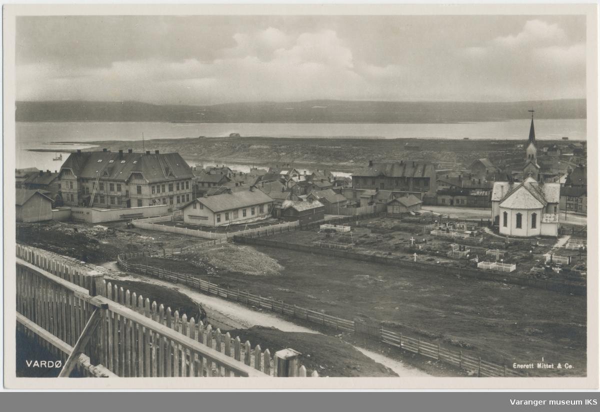 Postkort, byprospekt av Vardø sentrum, kirken og kirkegården i forgrunnen, sett fra Klondyke, Steilneset og fastlandet i bakgrunnen, ca. 1920