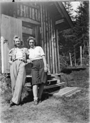 To kvinner utenfor ei hytte.