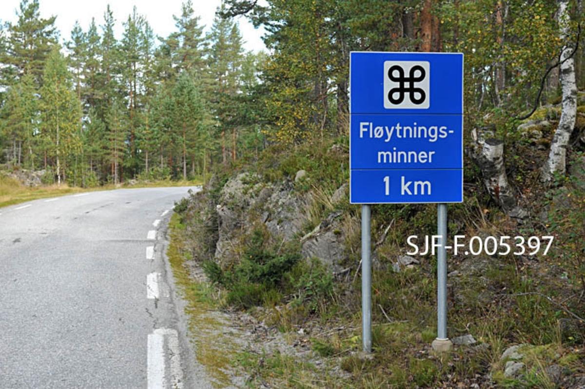 Informasjonsskilt om «fløytningsminner» ved riksveg 364 («Hovinvegen») i Notodden kommune i Telemark.  Det dreier seg om et blått skilt på to galvaniserte jernstolper.  Øverst på skiltet er det et kvitt kvadrat med en valknute – et kringleformet korssymbol – som viser at trafikantene nærmer seg severdigheter.  En kvit tekst under valknuten forteller at det dreier seg om «Fløytningsminner» med avkjøring fra Hovinvegen en kilometer lengre framme (ved Hegnadalen).  Kulturminnene det dreier seg om er Raudammen og Rautunnelen, hvor forholdene er tilrettelagt for publikum i form av en kultursti.