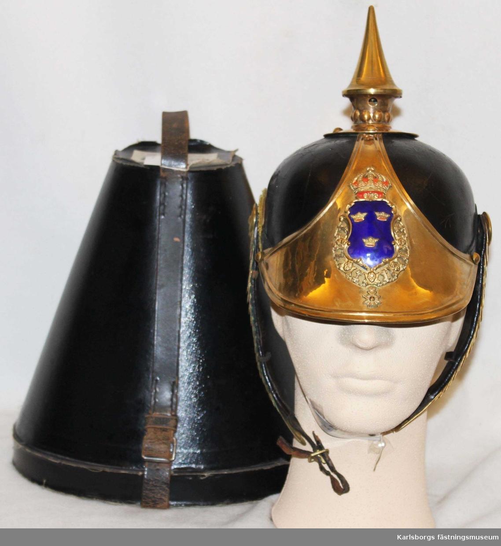 Kasken är gjord av lackerat läder med försivrade beslag och vapenplåt. På vapenplåten är riksvapnet i guld och emalj. Kasken ligger i tillhörande ask.