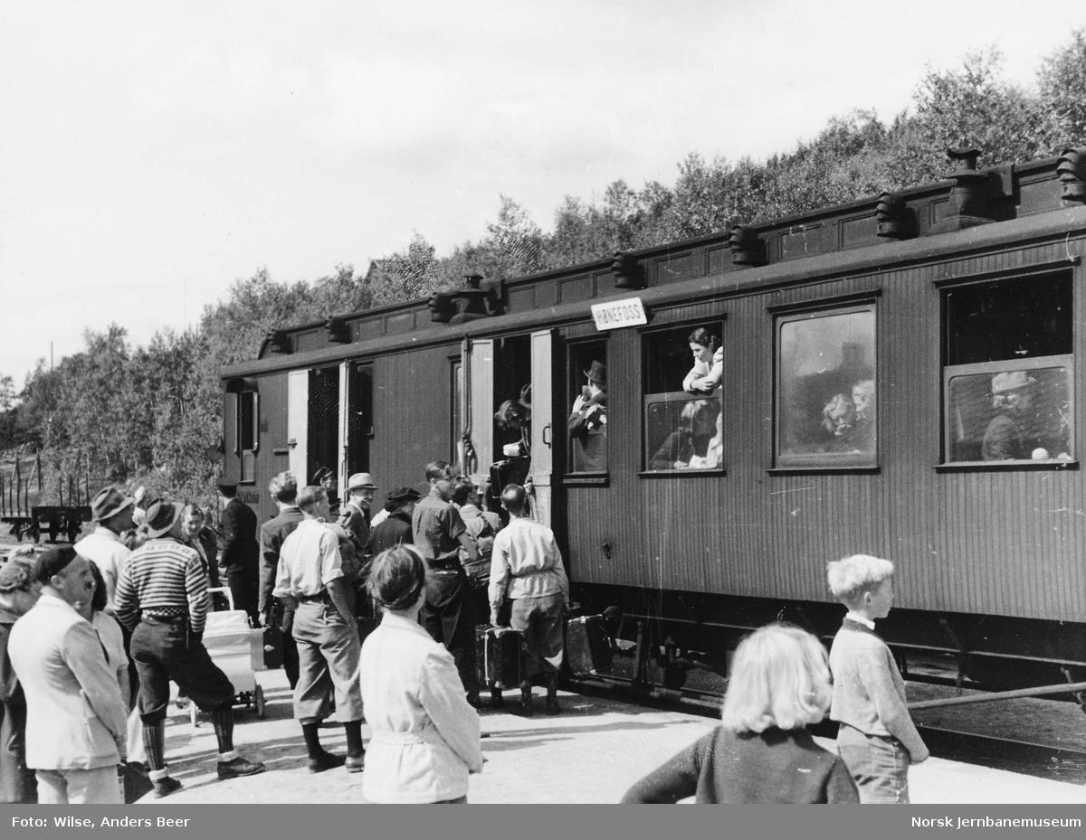 """Reisende stiger inn i godsrommet i en person- og konduktørvogn skiltet """"Hønefoss"""""""