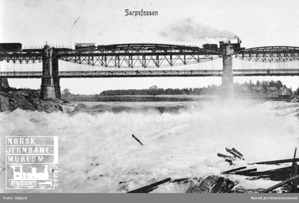 Godstog på brua over Sarpsfossen, trukket av damplokomotiv av type 9a