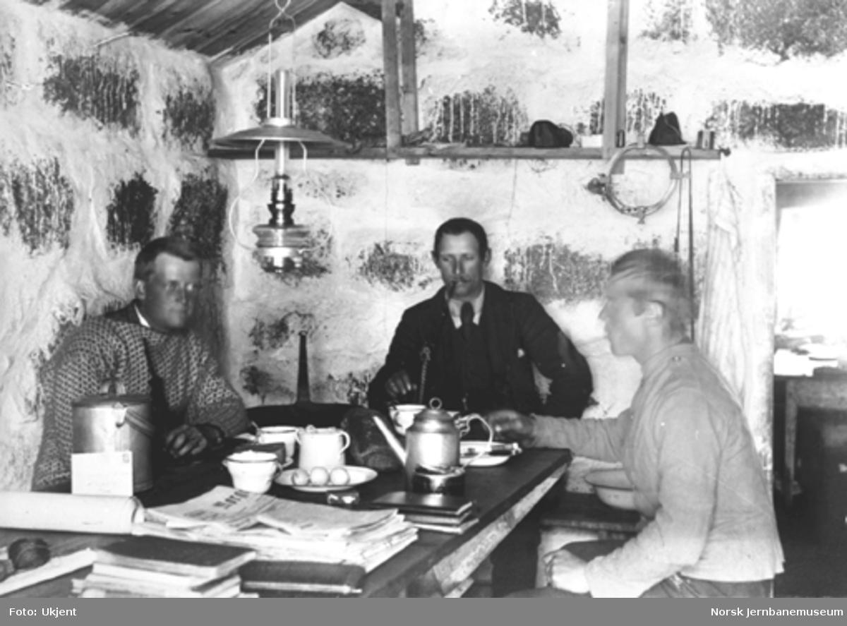 Bergensbanens anlegg; interiørbilde med tre personer ved kjøkkenbordet i brakke ved Låghellervatnet