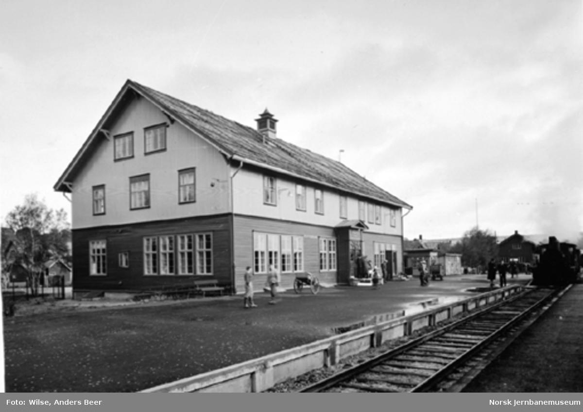 Røros stasjonsbygning med et damplokomotiv i spor 1