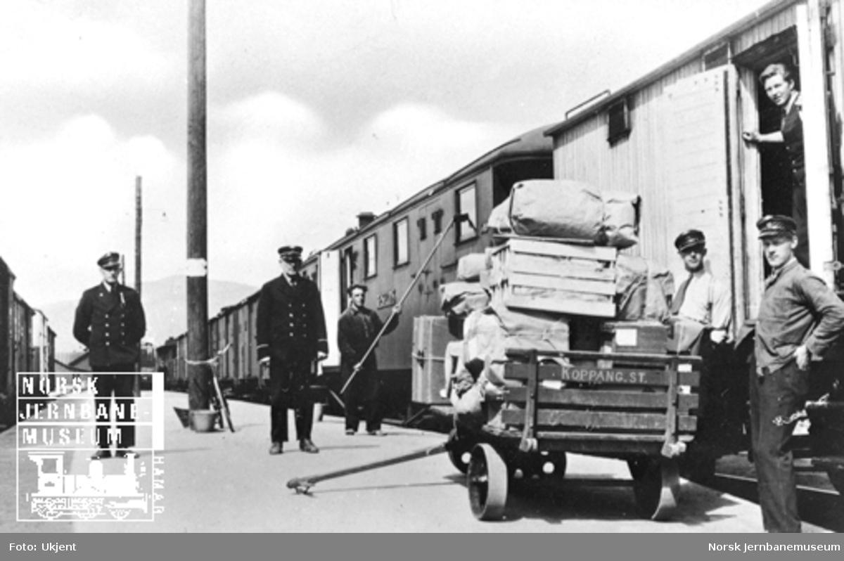 Personale på plattformen med normalsporet tog til høyre og smalsportoget til venstre. Utlasting av reisegods fra normalsporettoget.