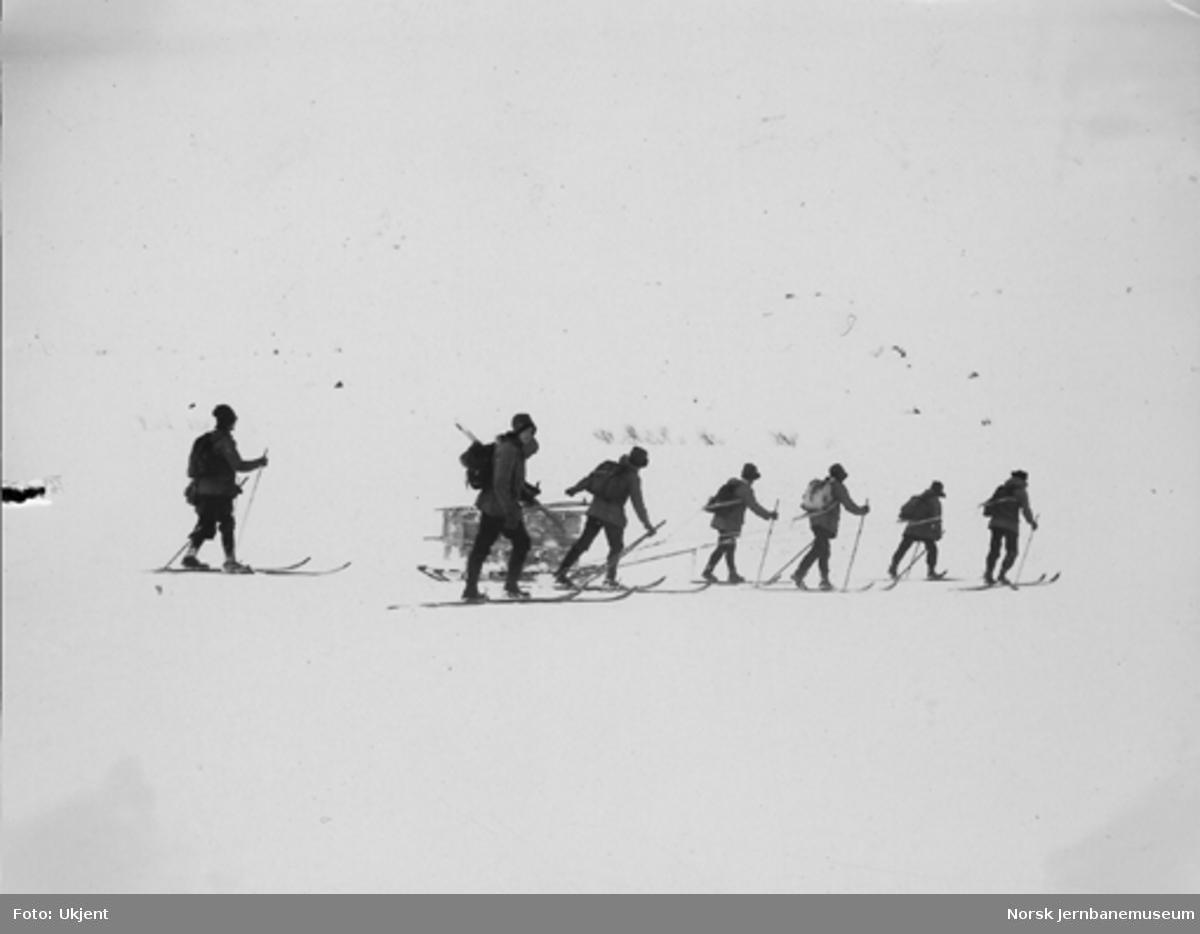 Snøblokade; sju mann på ski med utstyr