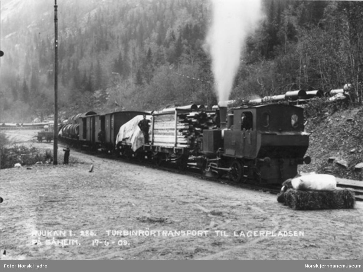 """Rjukanbanens damplokomotiv """"Odin"""" foran godstog, blant annet med turbinrør, på Rjukan"""
