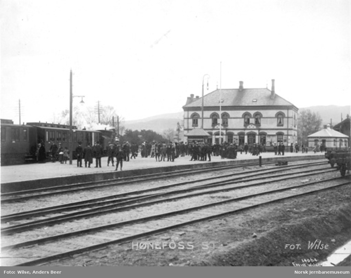 Hønefoss stasjon med toget til Oslo ved plattformen, mange reisende