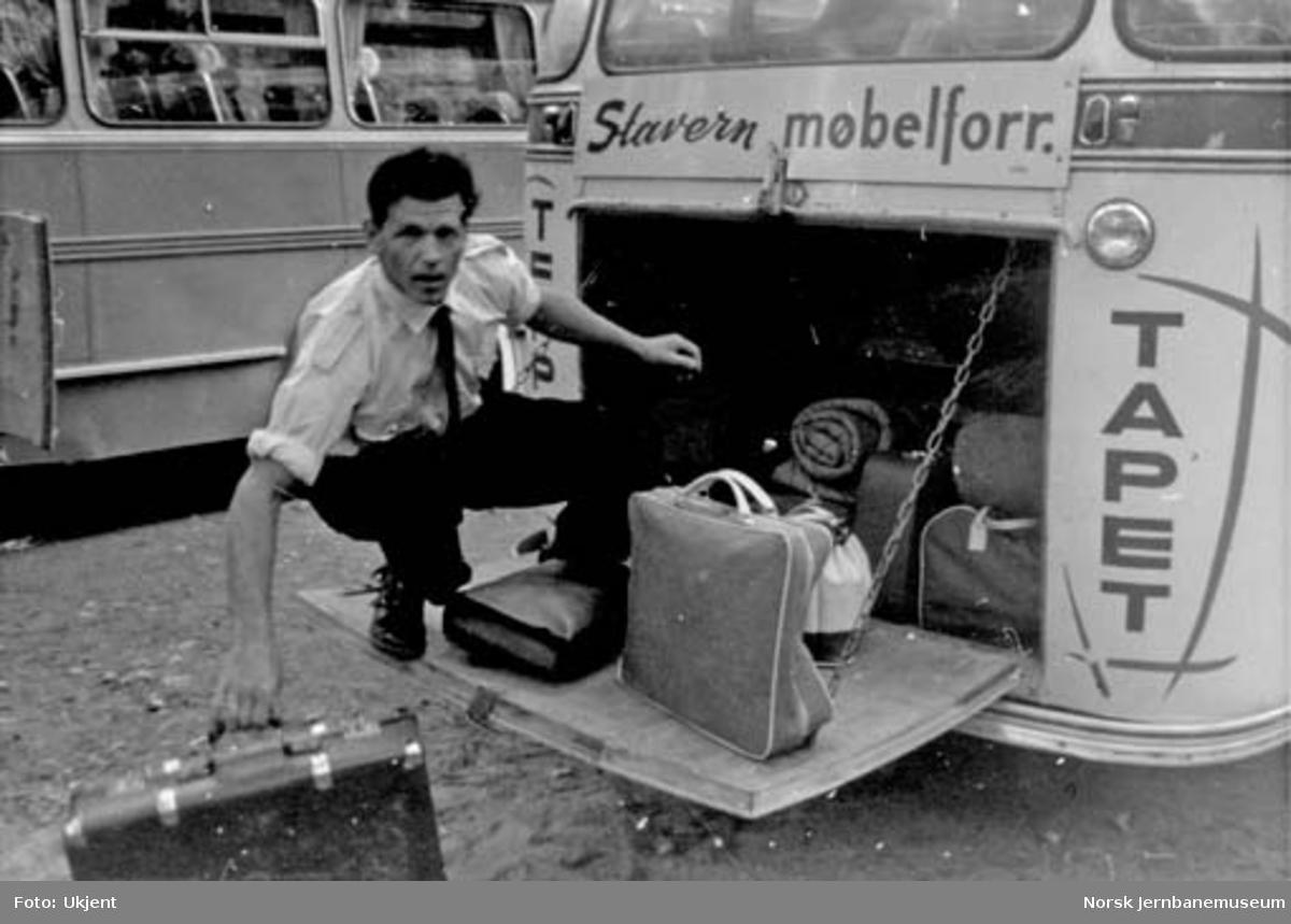 NSB Lågendalsruten : sjåfør Johan Søndreeng laster bagasje i bussens bagasjerom