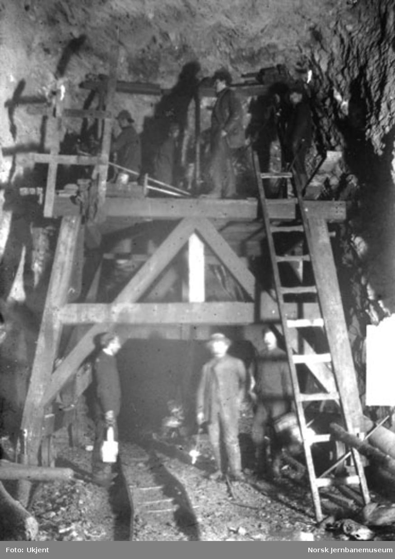 Anlegget av Gravehalsen tunnel; arbeidere på stillas i tunnelen