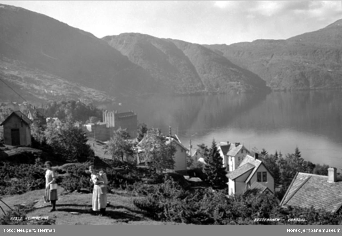 Oversiktsbilde over Vaksdal med Sørfjorden, to kvinner med melkespann i forgrunnen