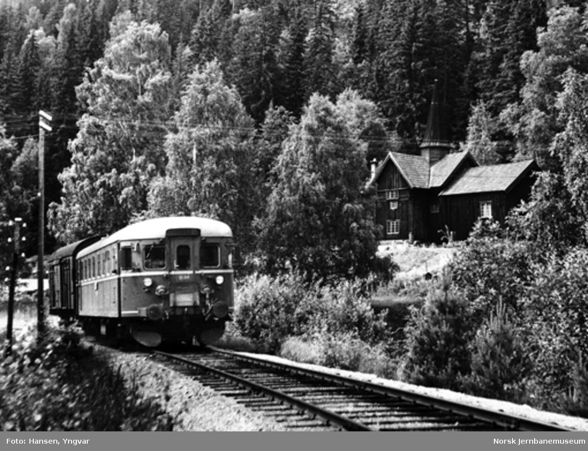 Motorvogntog på Numedalsbanen med Rollag stavkirke i bakgrunnen