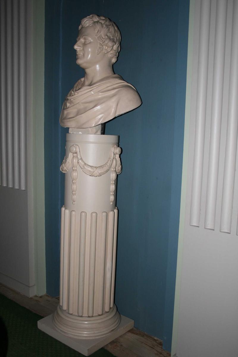 Kort krøllet hår, draperi rundt skuldrene som en romersk senator.