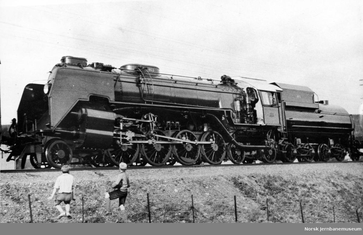 "Damplokomotiv type 49a nr. 463 ""Dovregubben"" under transport i godstog forbi Lillehammer"